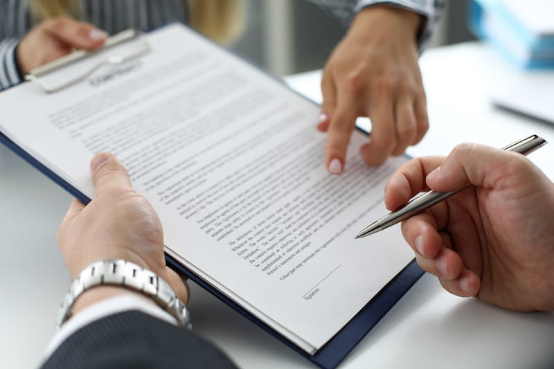 real estate clerk offering visitor document sign - Health and Safety